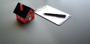 clipboard with pen near mini cardboard house